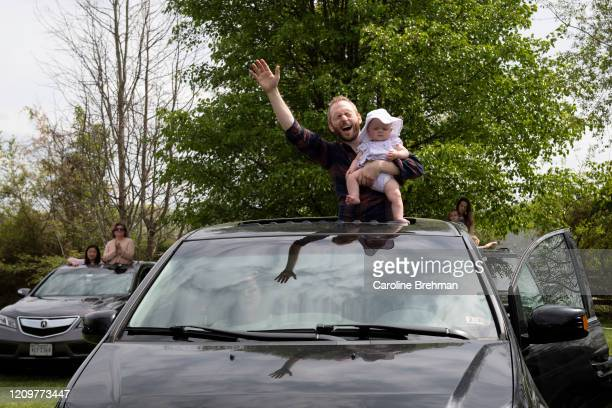 Man holds his baby as he sings during an Easter drive-in service at Glasgow Farm in Virginia due to the coronavirus outbreak on Sunday, April 12,...