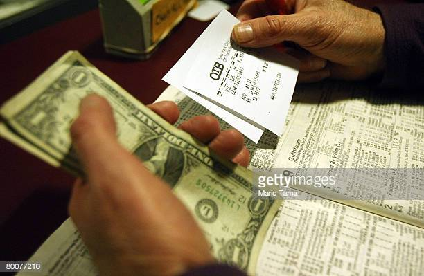 A man holds his betting slips and money at an OffTrack Betting parlor in Midtown Manhattan March 1 2008 in New York City The board that oversees New...