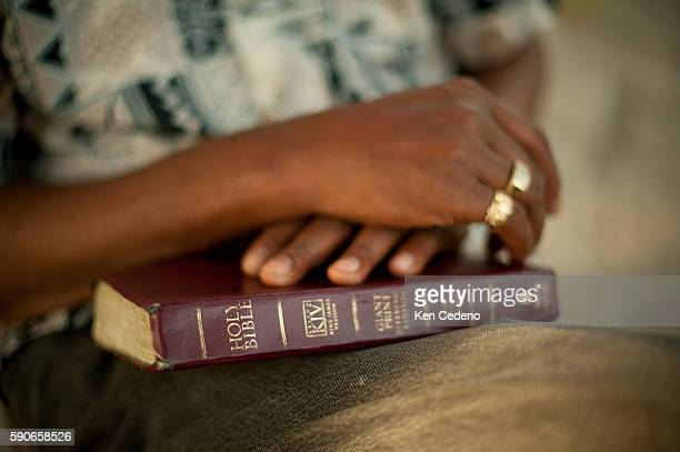 A man holds his bible in his lap during St Paul Church of God in Christ holds a tent revival in the lower 9th ward of New Orleans July 15 2010 Five...