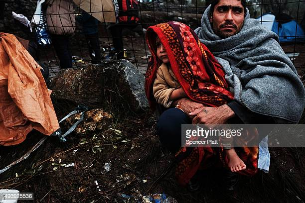 A man holds his child at the increasingly overwhelmed Moria camp on the island of Lesbos on October 23 2015 in Mitilini Greece Dozens of rafts and...