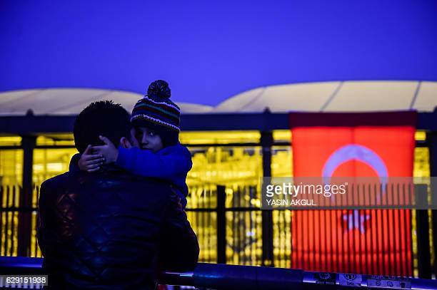 TOPSHOT A man holds his child next to Turkish national flag during a demonstration on December 11 2016 a day after twin bombings near the home...