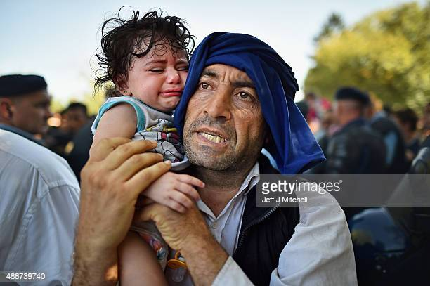 A man holds his crying child close to him as migrants force their way through police lines at Tovarnik station for a train to take them to Zagreb on...