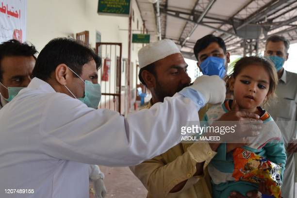 A man holds his daughter as a health official checks her body temperature amid concerns over the spread of the COVID19 novel coronavirus at Peshawar...