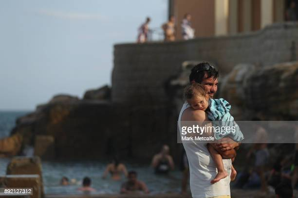 A man holds his daughter at Coogee Beach on December 14 2017 in Sydney Australia The bureau of meteorology has forecast temperatures over 40 degrees...