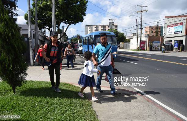 A man holds his daughter by the hand after picking her and his wife up at the Air Force base in Guatemala City on July 10 2018 after they were...