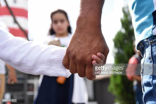TOPSHOT A man holds his daughter by the hand after picking her and his wife up at the Air Force base in Guatemala City on July 10 2018 after they...