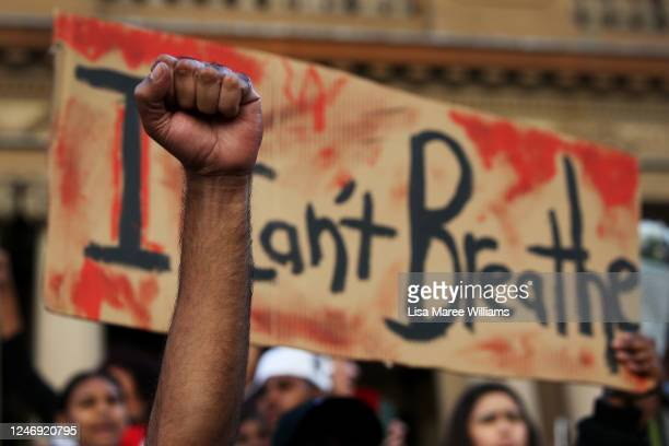 A man holds his fist in the air in front of a placard that reads 'I can't breathe' at Town Hall in solidarity with protests in the United States on...