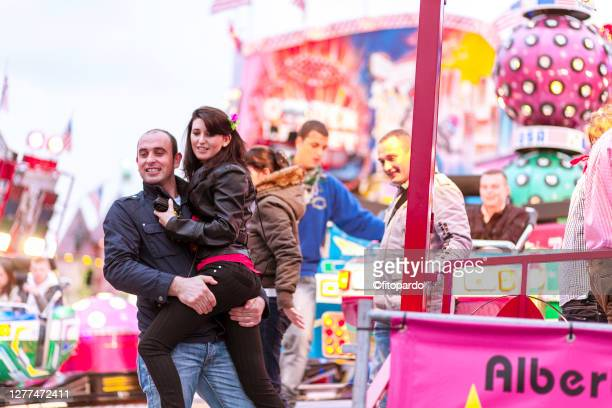 a man holds his girlfriend up toward him while exiting an attraction in the oktoberfest - bending over in skirt stock pictures, royalty-free photos & images