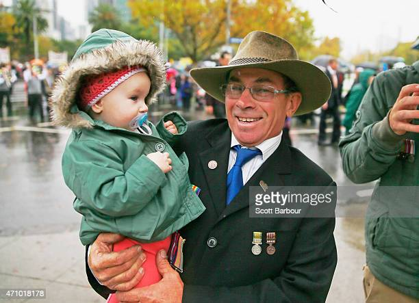 A man holds his granddaughter as they take part in the Anzac Day March on ANZAC Day at the Shrine of Remembrance on April 25 2015 in Melbourne...