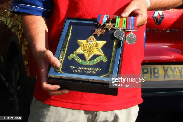 Man holds his grandfathers medals and Burma Star award during the commemoration The VE Day 75th anniversary when Victory in Europe over the Germans...
