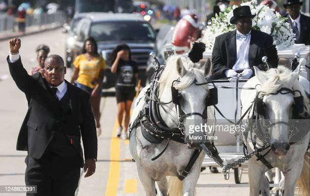 A man holds his hand up in solidarity as the remains of George Floyd are brought by horsedrawn carriage in a funeral procession to Houston Memorial...