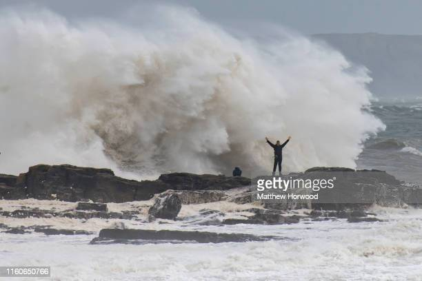A man holds his hands in the air as waves crash against the harbour wall on August 10 2019 in Porthcawl Wales The Met Office have issued a yellow...