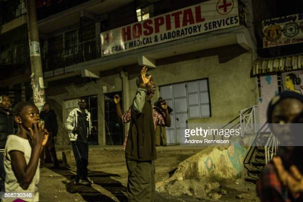 A man holds his hands up as he walks past police during unrest after election results were announced in the Mathare slum on October 30 2017 in...