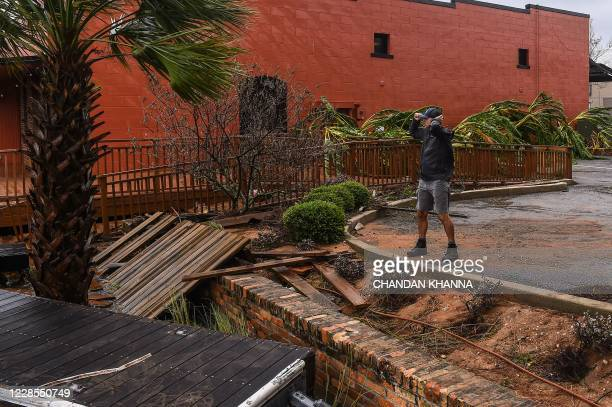 A man holds his hat in a strong wind during Hurricane Sally in downtown Pensacola Florida on September 16 2020 Hurricane Sally barrelled into the US...