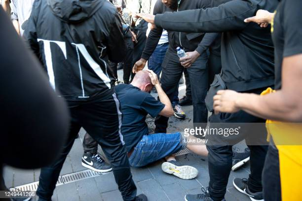 A man holds his head as he sits on the ground after a group of men carried him away after he was allegedly attacked by some of the crowd of...