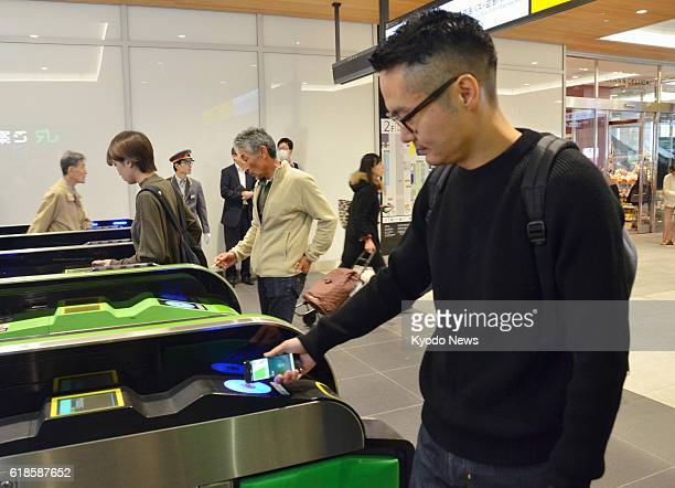 A man holds his iPhone above a card reader at an entrance gate at JR Shinjuku Station in Tokyo on Oct 25 paying for a transportation fee through...