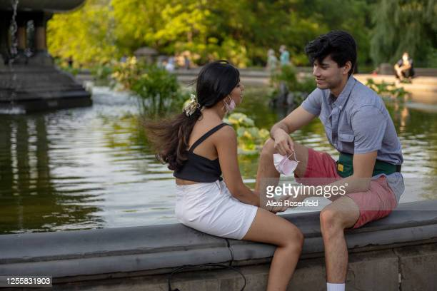 Man holds his mask in one hand while smiling at a girl at the Bethesda Fountain in Central Park as the city moves into Phase 3 of re-opening...