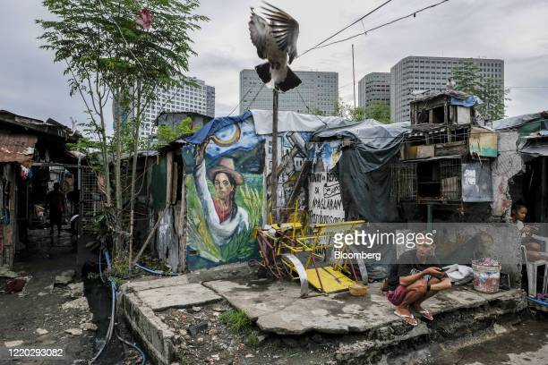 Man holds his mobile phone in the San Roque neighborhood as commercial high-rise buildings stand in the background in Quezon City, Metro Manila, the...