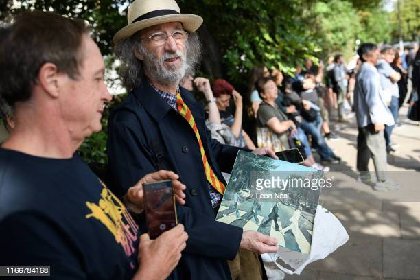 A man holds his original copy as members of the public recreate the iconic album cover for the Beatles album Abbey Road on the same pedestrian...