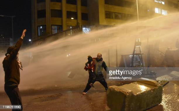 Man holds his son as security forces intervene in demonstrators with pressurized water and tear gas during a demonstration against the new Hassan...