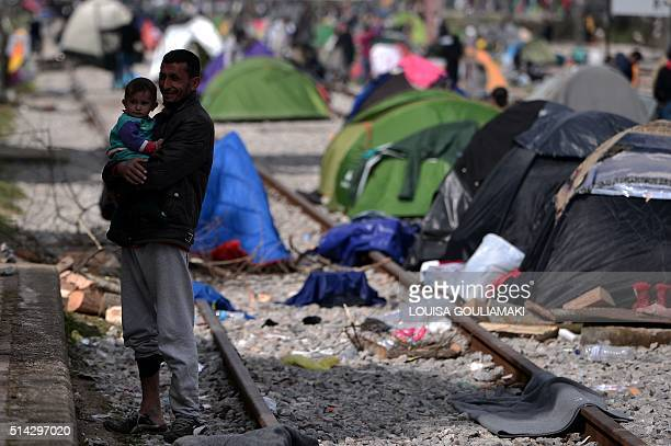 Man holds his son next to tents installed on railway tracks, at the makeshift camp of the Greek-Macedonian border, near the village of Idomeni on...