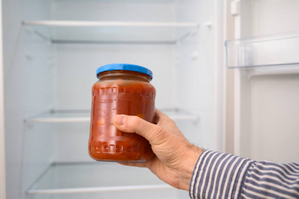 a man holds in front of  the refrigerator a glass pot of tomatoes. - opened can stock pictures, royalty-free photos & images