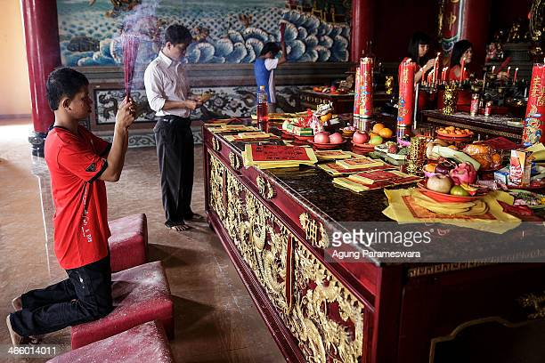 A man holds incense sticks as he attends prayers during Chinese New Year celebrations for the Year of The horse at Satya Dharma Temple on January 31...