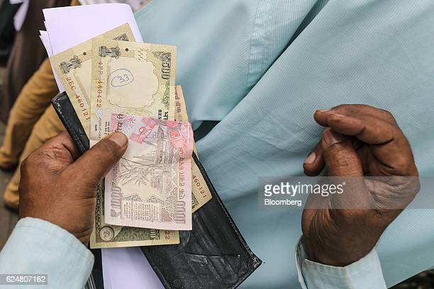 A man holds Indian one thousand and five hundred rupee banknotes as he stands in a line in a post office in Mumbai India on Friday Nov 18 2016...