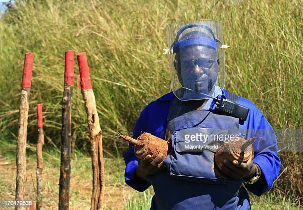 Man holds land mines from a field during de-mining operations to remove innumerable land mines planted during the civil war that injured thousands of...