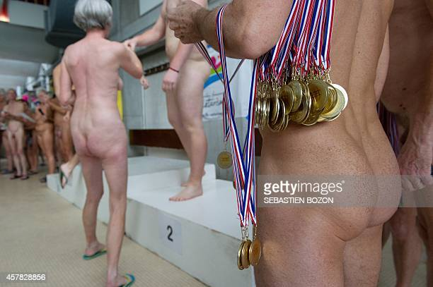 A man holds medals for the podium ceremony during a naturist swimming championship on October 25 2014 in Mulhouse eastern France AFP PHOTO /...