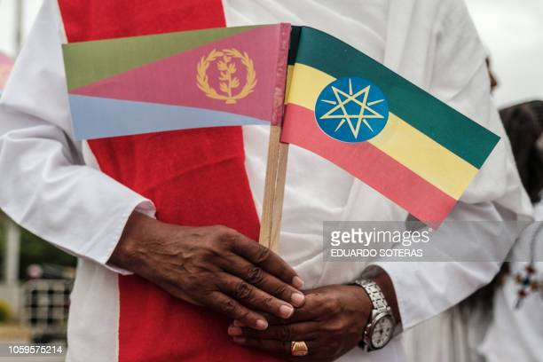 A man holds Narional flags of Eritrea and Ethiopia as he waits for the arrival of Eritrea's President at the airport in Gondar nothern Ethiopia on...