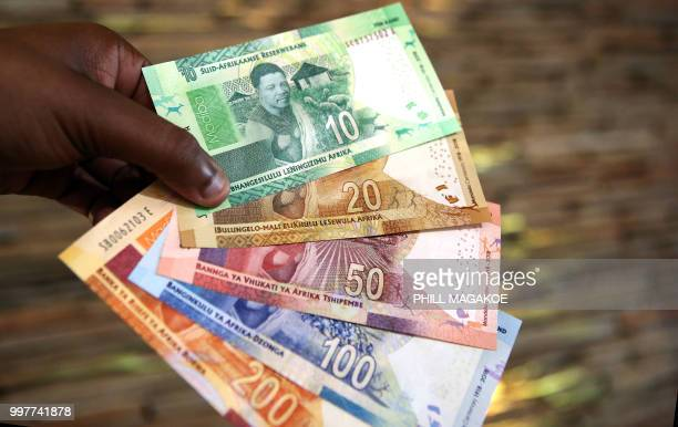 A man holds new South African banknotes at the value of ten twenty fifty one hundred and two hundred South African Rand depicting former South...
