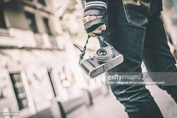 Man holds old-looking camera in hand when walking