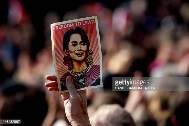 A man holds on June 16 2012 a poster of Myanmar opposition leader Aung San Suu Kyi during a public meeting following a ceremony where Suu Kyi...