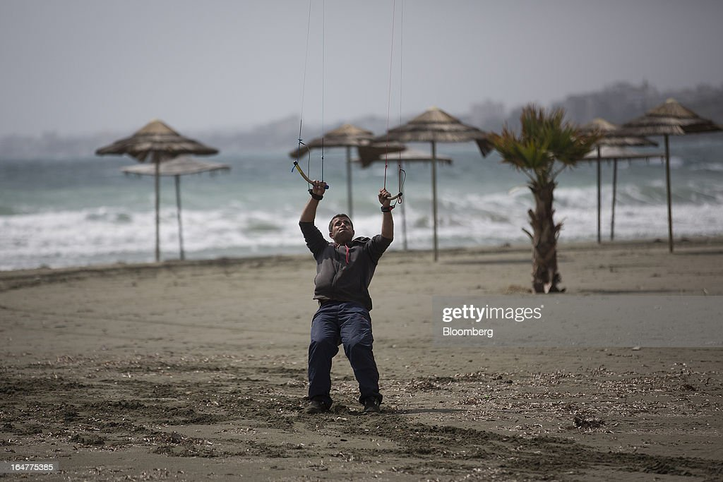 A man holds onto his kite in high winds on a deserted beach in Limassol, Cyprus, on Wednesday, March 27, 2013. The ECB said on March 25 it won't stop the Cypriot central bank from providing the island's banking sector with emergency funding. Photographer: Simon Dawson/Bloomberg via Getty Images