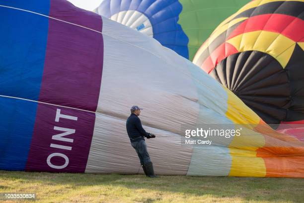 A man holds onto ropes as a hot air balloon is inflated at Longleat's Sky Safari at Longleat on September 15 2018 near Warminster in Wiltshire...