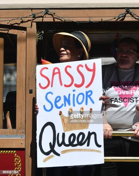 A man holds out a sign while rolling in a trolly car during the San Francisco gay pride parade in San Francisco California on June 2018