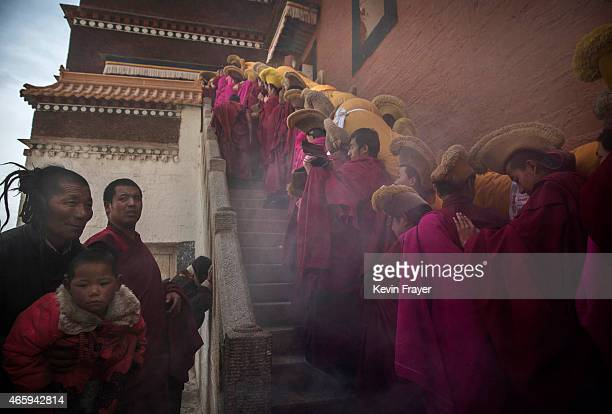 A man holds out his sin for a blessing asTibetan Buddhist Monks of the Gelug or Yellow Hat order carry a large thangka of Buddha after showing it to...