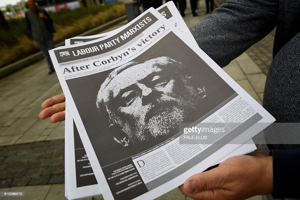 A man holds out newsletters with an image of British Labour party leader Jeremy Corbyn on the front outside the entrance to the annual Labour Party conference in Liverpool, north west England on September 25, 2016. / AFP / PAUL