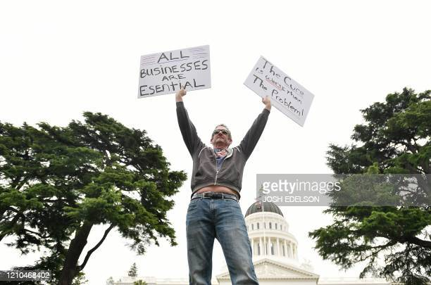 TOPSHOT A man holds out signs as hundreds of people gather to protest in spite of shelterinplace rules still being in effect at California's state...