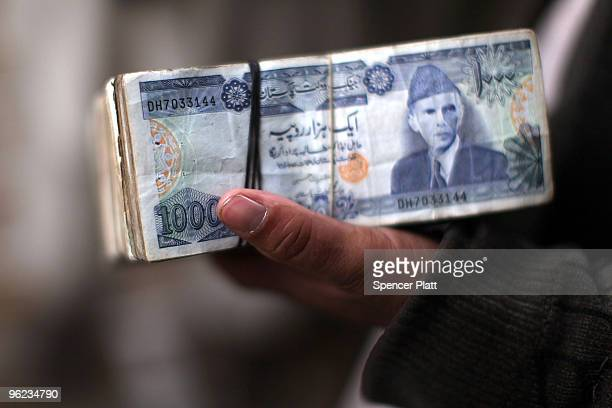A man holds Pakistani currency in a money market on January 28 2010 in Kabul Afghanistan London is hosting a critical daylong international...