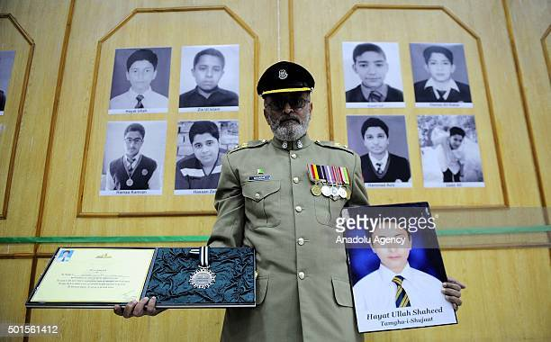 A man holds picture of a victim one of the students of Army Public School killed by Taliban militants before displaying it in a gallery dedicated by...