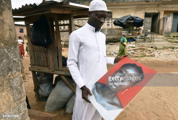 TOPSHOT A man holds portrait of one of seven women killed on March 3 when security forces loyal to Ivory Coast's former president Laurent Gbagbo...