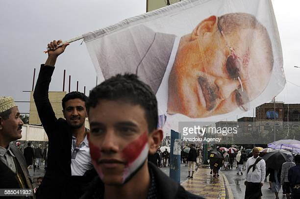 A man holds poster as people gather to support the 'supreme council' which was established for state affairs by Houthi and former President Ali...