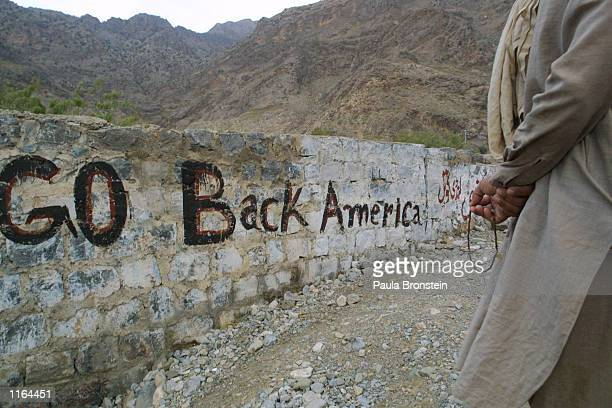 A man holds prayer beads near a stone wall that reads Go Back America September 20 2001 near the Khyber Pass on the Pakistani border with Afghanistan...