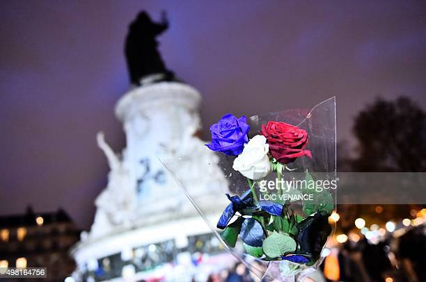 A man holds roses in the colours of the French national flag at Place de la Republique in Paris on November 21 2015 as he arrives to pay tribute to...