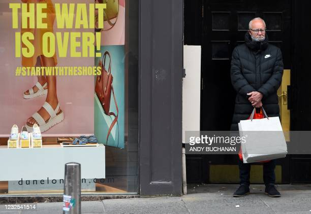 Man holds shopping bags as he waits outside a re-opened shoe shop in Glasgow on April 26, 2021 following the relaxing of some Covid-19 restrictions...