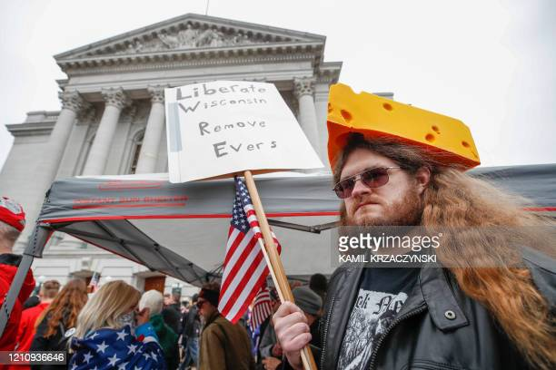 A man holds sign during a protest against the coronavirus shutdown in front of State Capitol in Madison Wisconsin on April 24 2020 Gyms hair salons...