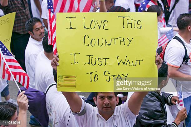 Man holds sign saying 'I love this country' along with hundreds of thousands of immigrants participating in march for Immigrants and Mexicans...