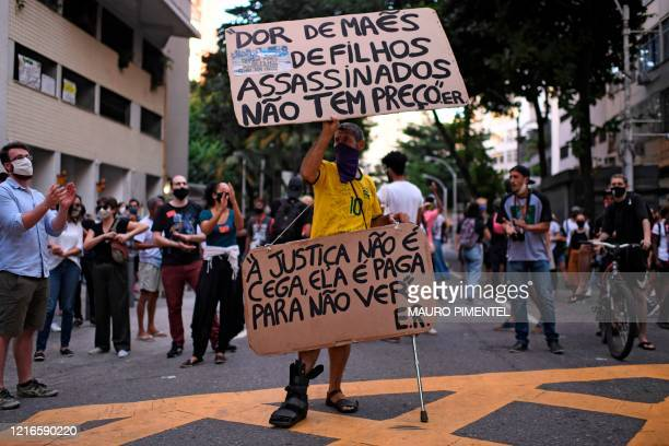 A man holds signs reading The pain of children murdered has no price and Justice is not blind it is paid not to see during a protest called by...